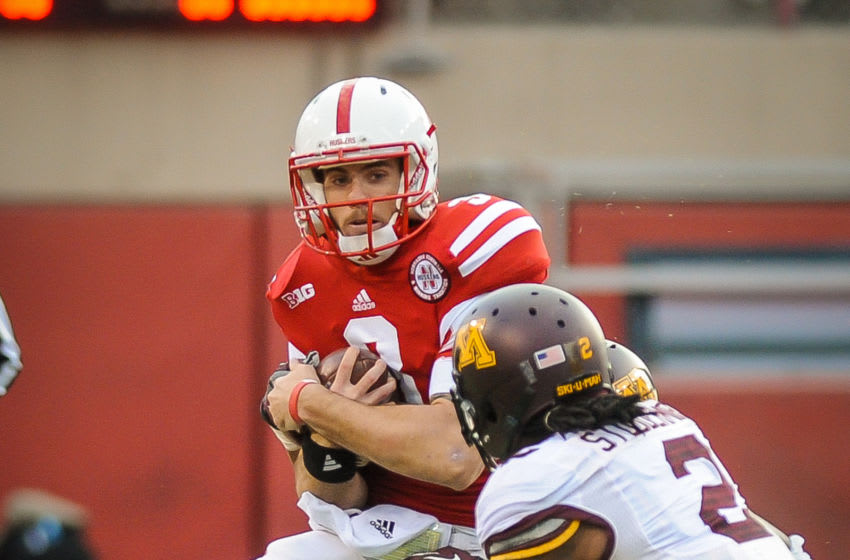 LINCOLN, NE - NOVEMBER 17: Quarterback Taylor Martinez #3 of the Nebraska Cornhuskers covers up the ball before taking a hit from defensive back Troy Stoudermire #2 of the Minnesota Golden Gophers during their game at Memorial Stadium on November 17, 2012 in Lincoln, Nebraska. (Photo by Eric Francis/Getty Images)