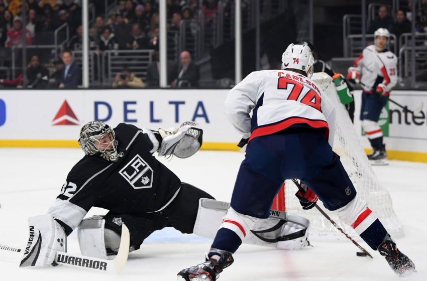 LOS ANGELES, CALIFORNIA - DECEMBER 04: John Carlson #74 of the Washington Capitals deeks Jonathan Quick #32 of the Los Angeles Kings, for his second goal of the game and a 2-0 lead, during the first period at Staples Center on December 04, 2019 in Los Angeles, California. (Photo by Harry How/Getty Images)