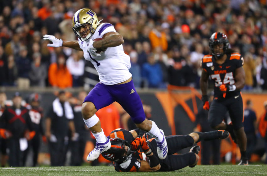CORVALLIS, OREGON - NOVEMBER 08: Hunter Bryant #1 of the Washington Huskies breaks a tackle against David Morris #24 of the Oregon State Beavers in the second quarter during their game at Reser Stadium on November 08, 2019 in Corvallis, Oregon. (Photo by Abbie Parr/Getty Images)