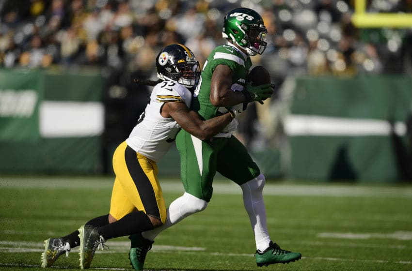 EAST RUTHERFORD, NEW JERSEY - DECEMBER 22: Le'Veon Bell #26 of the New York Jets is tackled by Devin Bush #55 of the Pittsburgh Steelers after a reception during the first half at MetLife Stadium on December 22, 2019 in East Rutherford, New Jersey. (Photo by Steven Ryan/Getty Images)