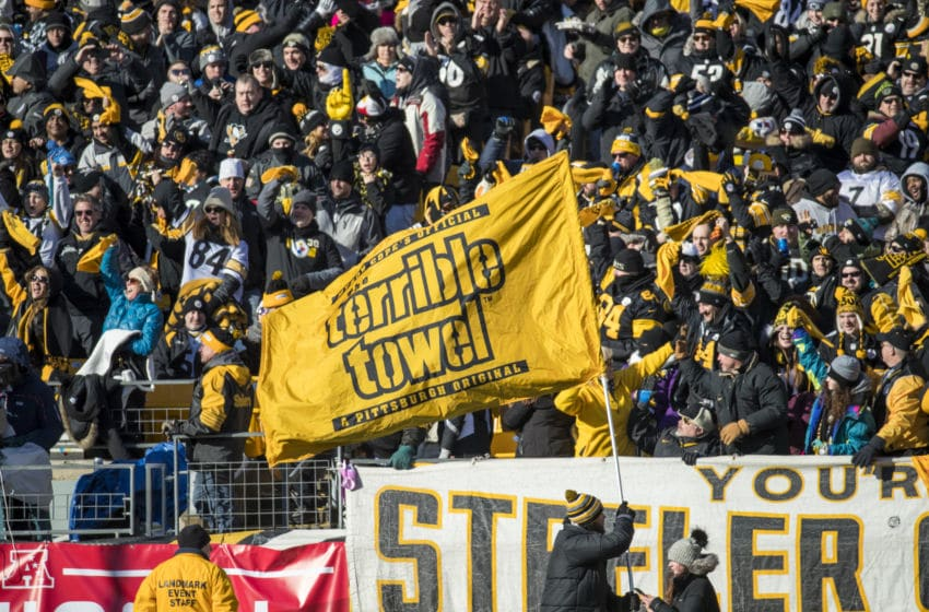 PITTSBURGH, PA - JANUARY 14: Pittsburgh Steelers fans cheer as a stadium staff member waves a Terrible Towel flag during the second quarter against the Jacksonville Jaguars in the AFC Divisional Playoff game at Heinz Field on January 14, 2018 in Pittsburgh, Pennsylvania. Jaguars defeat Pittsburgh 45-42. (Photo by Brett Carlsen/Getty Images) *** Local Caption ***