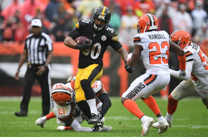 CLEVELAND, OH - SEPTEMBER 09: James Conner #30 of the Pittsburgh Steelers carries the ball between the defense of Denzel Ward #21 and Damarious Randall #23 of the Cleveland Browns during the fourth quarter at FirstEnergy Stadium on September 9, 2018 in Cleveland, Ohio. (Photo by Jason Miller/Getty Images)