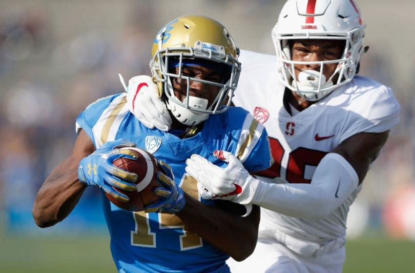 PASADENA, CA - NOVEMBER 24: Theo Howard #14 of the UCLA Bruins eludes the defense of Kendall Williamson #29 of the Stanford Cardinal on a pass play during the first half of a game at the Rose Bowl on November 24, 2018 in Pasadena, California. (Photo by Sean M. Haffey/Getty Images)