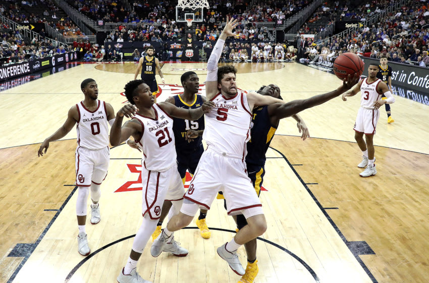 KANSAS CITY, MISSOURI - MARCH 13: Matt Freeman #5 of the Oklahoma Sooners and Andrew Gordon #12 of the West Virginia Mountaineers compete for a rebound during the first round game of the Big 12 Basketball Tournament at the Sprint Center on March 13, 2019 in Kansas City, Missouri. (Photo by Jamie Squire/Getty Images)