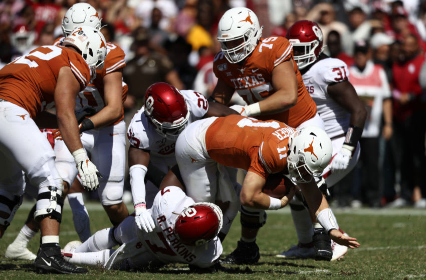 DALLAS, TEXAS - OCTOBER 12: Sam Ehlinger #11 of the Texas Longhorns is tackled by Ronnie Perkins #7 of the Oklahoma Sooners during the 2019 AT&T Red River Showdown at Cotton Bowl on October 12, 2019 in Dallas, Texas. (Photo by Ronald Martinez/Getty Images)