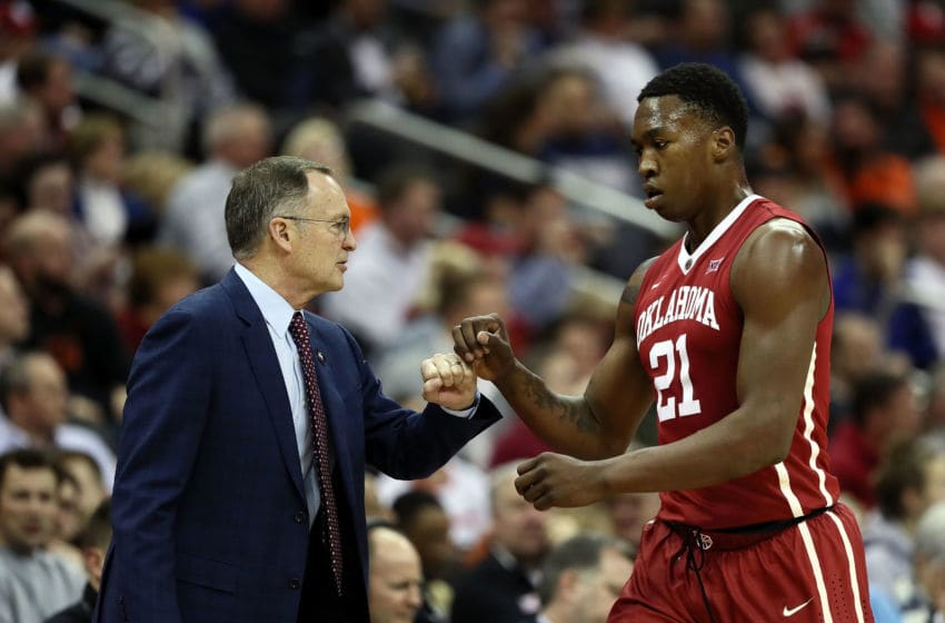 KANSAS CITY, MO - MARCH 07: Head coach Lon Kruger of the Oklahoma Sooners fist bumps Kristian Doolittle #21 during the first round of the Big 12 Basketball Tournament against the Oklahoma State Cowboys at the Sprint Center on March 7, 2018 in Kansas City, Missouri. (Photo by Jamie Squire/Getty Images)