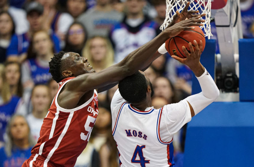 Feb 15, 2020; Lawrence, Kansas, USA; Kansas Jayhawks guard Isaiah Moss (4) is fouled while shooting by Oklahoma Sooners forward Kur Kuath (52) during the first half at Allen Fieldhouse. Mandatory Credit: Jay Biggerstaff-USA TODAY Sports