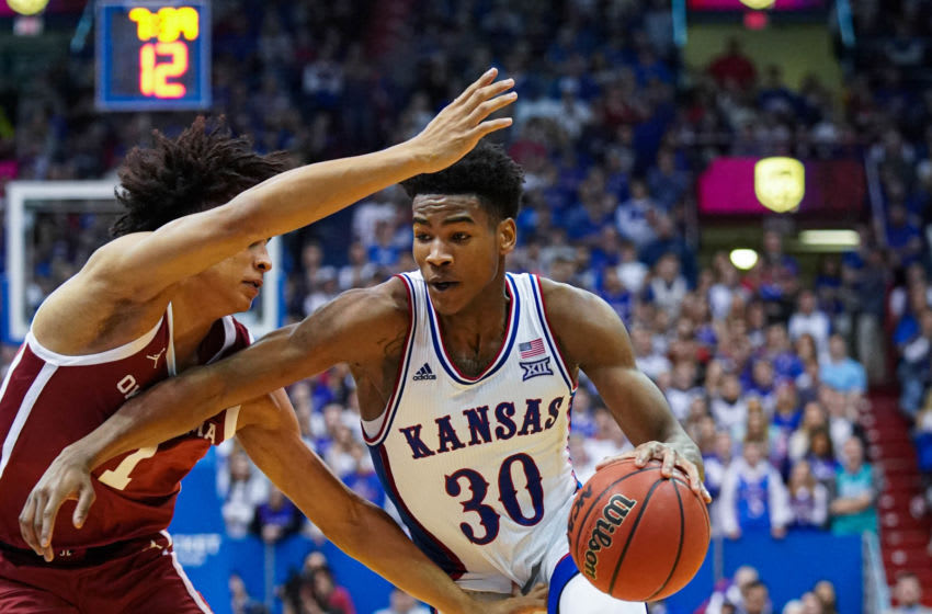 Feb 15, 2020; Lawrence, Kansas, USA; Kansas Jayhawks guard Ochai Agbaji (30) drives against Oklahoma Sooners forward Jalen Hill (1) during the second half at Allen Fieldhouse. Mandatory Credit: Jay Biggerstaff-USA TODAY Sports