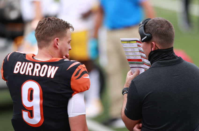 CINCINNATI, OHIO - SEPTEMBER 13: Quarterback Joe Burrow #9 of the Cincinnati Bengals looks on with a coach against the Los Angeles Chargers during the first half at Paul Brown Stadium on September 13, 2020 in Cincinnati, Ohio. (Photo by Bobby Ellis/Getty Images)