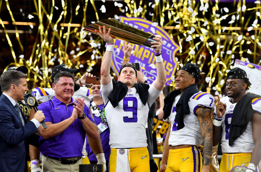 NEW ORLEANS, LOUISIANA - JANUARY 13: Joe Burrow of the LSU Tigers raises the National Championship Trophy with Ed Orgeron, Grant Delpit #7, and Patrick Queen #8 after the College Football Playoff National Championship game at the Mercedes Benz Superdome on January 13, 2020 in New Orleans, Louisiana. The LSU Tigers topped the Clemson Tigers, 42-25. (Photo by Alika Jenner/Getty Images)