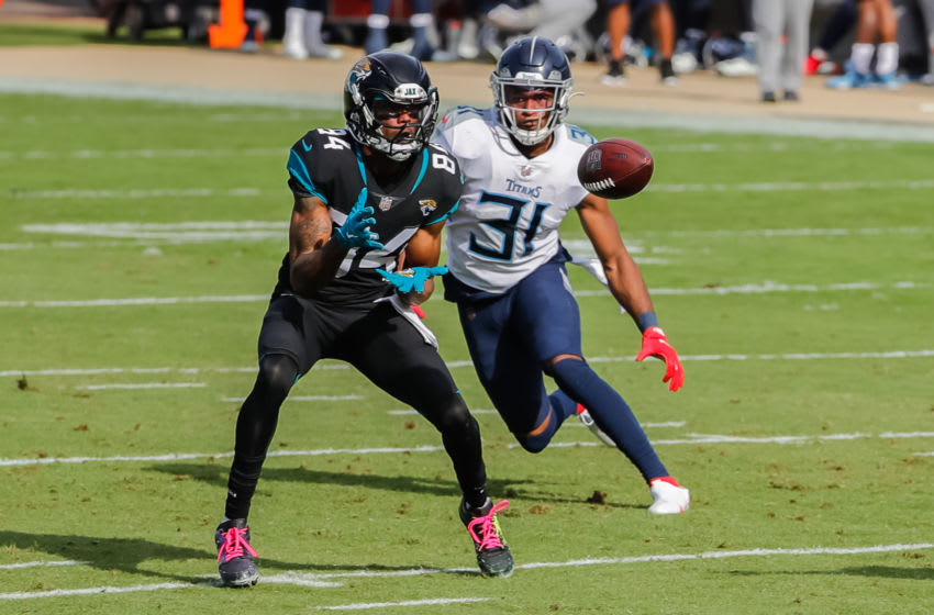 Dec 13, 2020; Jacksonville, Florida, USA; Jacksonville Jaguars wide receiver Keelan Cole (84) catches the ball as Tennessee Titans free safety Kevin Byard (31) closes in during the second quarter at TIAA Bank Field. Mandatory Credit: Mike Watters-USA TODAY Sports