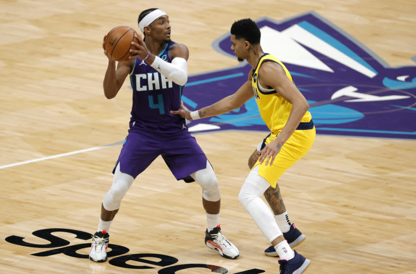 CHARLOTTE, NORTH CAROLINA - JANUARY 27: Devonte' Graham #4 of the Charlotte Hornets is closely guarded by Jeremy Lamb #26 of the Indiana Pacers during the third quarter of their game at Spectrum Center on January 27, 2021 in Charlotte, North Carolina. NOTE TO USER: User expressly acknowledges and agrees that, by downloading and or using this photograph, User is consenting to the terms and conditions of the Getty Images License Agreement. (Photo by Jared C. Tilton/Getty Images)
