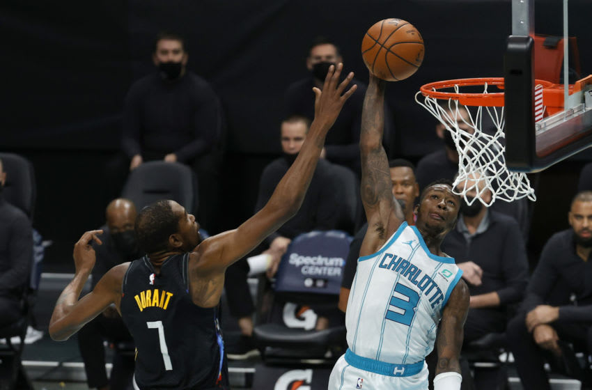 CHARLOTTE, NORTH CAROLINA - DECEMBER 27: Terry Rozier #3 of the Charlotte Hornets dunks the ball against Kevin Durant #7 of the Brooklyn Nets during the third quarter of their game at Spectrum Center on December 27, 2020 in Charlotte, North Carolina. NOTE TO USER: User expressly acknowledges and agrees that, by downloading and or using this photograph, User is consenting to the terms and conditions of the Getty Images License Agreement. (Photo by Jared C. Tilton/Getty Images)