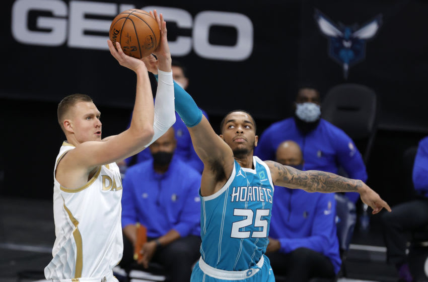 CHARLOTTE, NORTH CAROLINA - JANUARY 13: Kristaps Porzingis #6 of the Dallas Mavericks attempts a shot against P.J. Washington #25 of the Charlotte Hornets during the fourth quarter of their game at Spectrum Center on January 13, 2021 in Charlotte, North Carolina. NOTE TO USER: User expressly acknowledges and agrees that, by downloading and or using this photograph, User is consenting to the terms and conditions of the Getty Images License Agreement. (Photo by Jared C. Tilton/Getty Images)