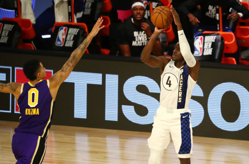 Aug 8, 2020; Lake Buena Vista, Florida, USA; Indiana Pacers guard Victor Oladipo (4) shoots the ball against Los Angeles Lakers forward Kyle Kuzma (0) during the second quarter in a NBA basketball game at The Field House. Mandatory Credit: Kim Klement-USA TODAY Sports