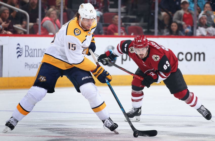 GLENDALE, ARIZONA - OCTOBER 17: Craig Smith #15 of the Nashville Predators skates with the puck ahead of Conor Garland #83 of the Arizona Coyotes during the first period of the NHL game at Gila River Arena on October 17, 2019 in Glendale, Arizona. (Photo by Christian Petersen/Getty Images)