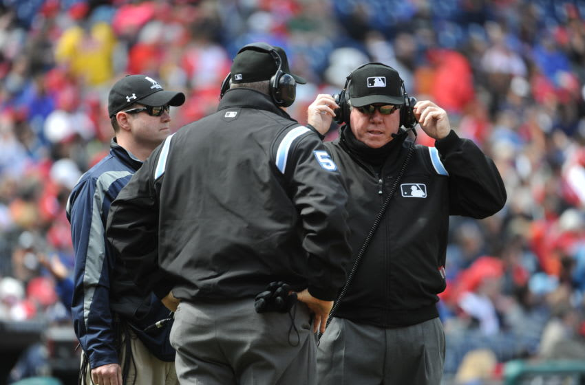 MLB umpires with headphones on listening to an instant replay review (Photo by Rich Pilling/Getty Images)