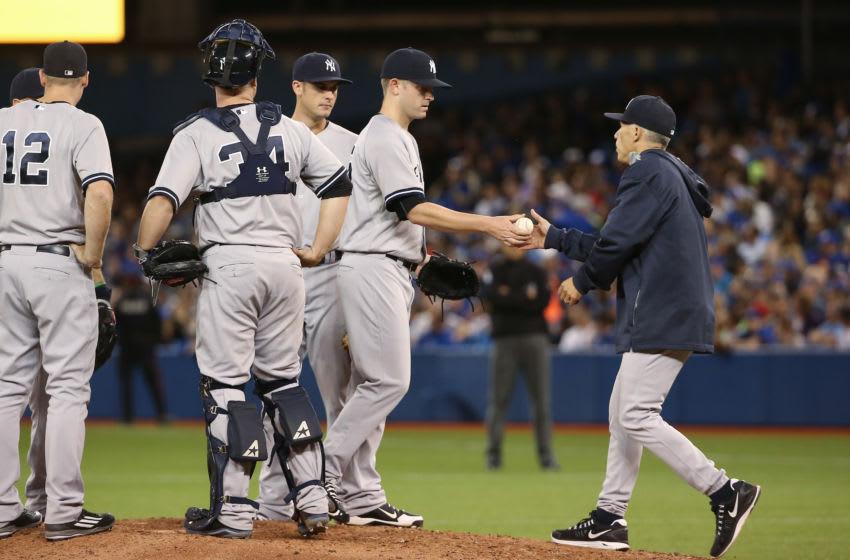 Caleb Cotham #65 and Joe Girardi #28 of the New York Yankees (Photo by Tom Szczerbowski/Getty Images)