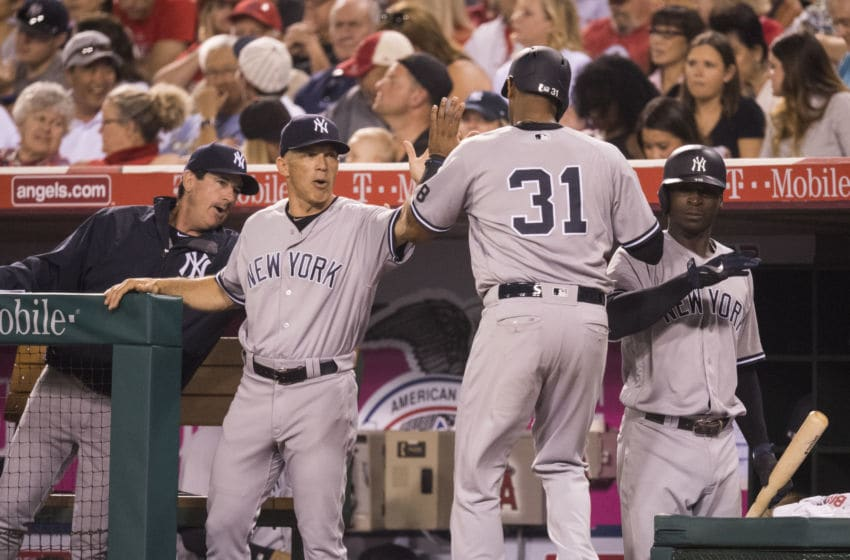 ANAHEIM, CA - AUGUST 19: Bench coach Rob Thomson #59, manager Joe Girardi #28, Aaron Hicks #31 and Didi Gregorius #18 of the New York Yankees celebrate after Hicks scored on a RBI single by Ronald Torreyes during the sixth inning of the game against the Los Angeles Angels of Anaheim at Angel Stadium of Anaheim on August 19, 2016 in Anaheim, California. (Photo by Matt Brown/Angels Baseball LP/Getty Images)