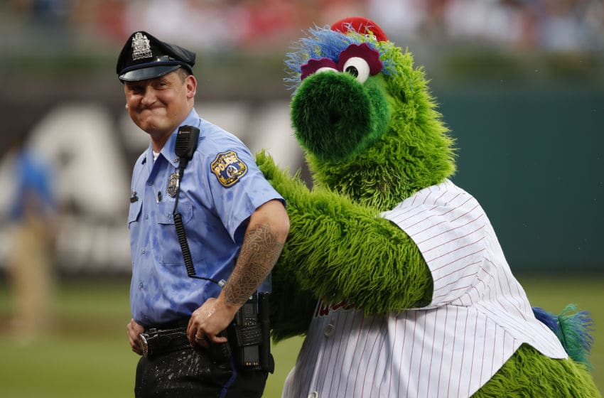 PHILADELPHIA, PA - JULY 21: The Phillie Phanatic shields himself behind a police officer after players from the Milwaukee Brewers threw cups of water at him before a game against the Philadelphia Phillies at Citizens Bank Park on July 21, 2017 in Philadelphia, Pennsylvania. (Photo by Rich Schultz/Getty Images)