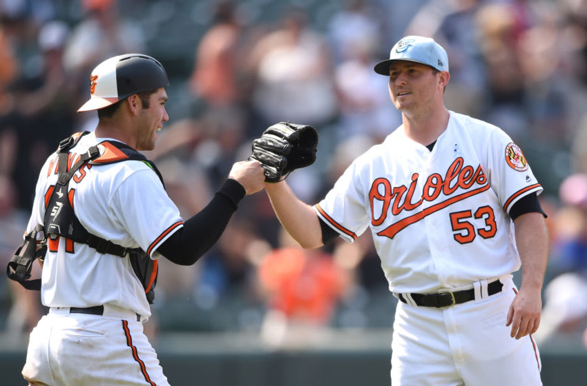 BALTIMORE, MD - JUNE 17: Zach Britton #53 of the Baltimore Orioles celebrates a win with Austin Wynns #61 after a baseball game against the Miami Marlins at Oriole Park at Camden Yards on June 17, 2018 in Baltimore, Maryland. (Photo by Mitchell Layton/Getty Images)