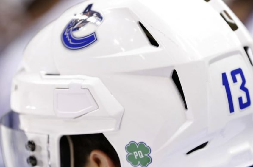 Dec 2, 2014; Washington, DC, USA; Vancouver Canucks center Nick Bonino (13) displays a sticker on his helmet in memory of late Hall of Famer and Canuck great Pat Quinn against the Washington Capitals in the third period at Verizon Center. The Canucks won 4-3. Mandatory Credit: Geoff Burke-USA TODAY Sports