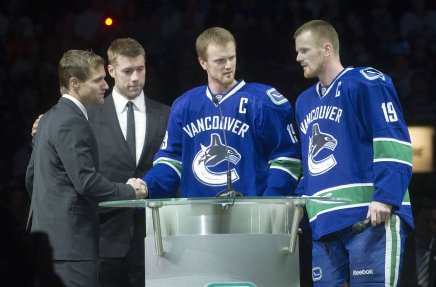 VANCOUVER, CANADA - DECEMBER 11: Henrik Sedin #33 and Daniel Sedin #22 of the Vancouver Canucks along with Mattias Ohlund #5 of the Tampa Bay Lightning greet former Canuck Markus Naslund during a pre-game ceremony to retire Naslund's jersey prior to NHL action on December 11, 2010 at Rogers Arena in Vancouver, BC, Canada. (Photo by Rich Lam/Getty Images)