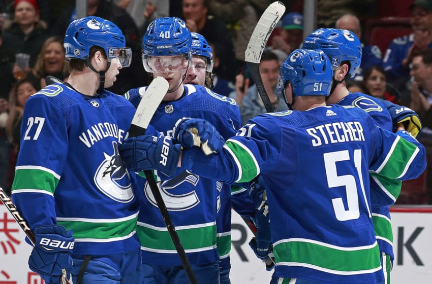 VANCOUVER, BC - FEBRUARY 11: Bo Horvat #53 of the Vancouver Canucks is congratulated by teammates Ben Hutton #27, Elias Pettersson #40, and Troy Stecher #51 after scoring during their NHL game against the San Jose Sharks at Rogers Arena February 11, 2019 in Vancouver, British Columbia, Canada. (Photo by Jeff Vinnick/NHLI via Getty Images)