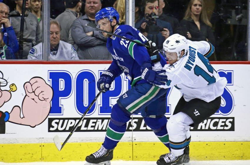 VANCOUVER, BC - APRIL 2: Gustav Nyquist #14 of the San Jose Sharks checks Alexander Edler #23 of the Vancouver Canucks during their NHL game at Rogers Arena April 2, 2019 in Vancouver, British Columbia, Canada. Vancouver won 4-2. (Photo by Jeff Vinnick/NHLI via Getty Images)