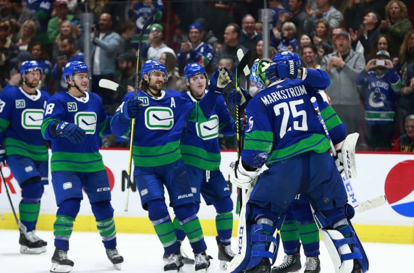 VANCOUVER, BC - OCTOBER 12: Jacob Markstrom #25 of the Vancouver Canucks is congratulated by teammates after winning their NHL game against the Philadelphia Flyers at Rogers Arena October 12, 2019 in Vancouver, British Columbia, Canada. Vancouver won 3-2 in a shootout. (Photo by Jeff Vinnick/NHLI via Getty Images)