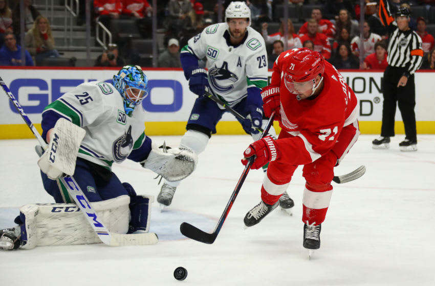 DETROIT, MICHIGAN - OCTOBER 22: Dylan Larkin #71 of the Detroit Red Wings tries to get a shot off on Jacob Markstrom #25 of the Vancouver Canucks during the second period at Little Caesars Arena on October 22, 2019 in Detroit, Michigan. Vancouver won the game 5-2. (Photo by Gregory Shamus/Getty Images)
