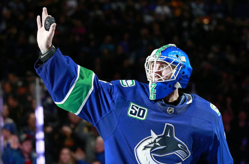 VANCOUVER, BC - DECEMBER 12: Jacob Markstrom #25 of the Vancouver Canucks holds up a puck while being named first star after their NHL game against the Carolina Hurricanes at Rogers Arena December 12, 2019 in Vancouver, British Columbia, Canada. Vancouver won 1-0. (Photo by Jeff Vinnick/NHLI via Getty Images)