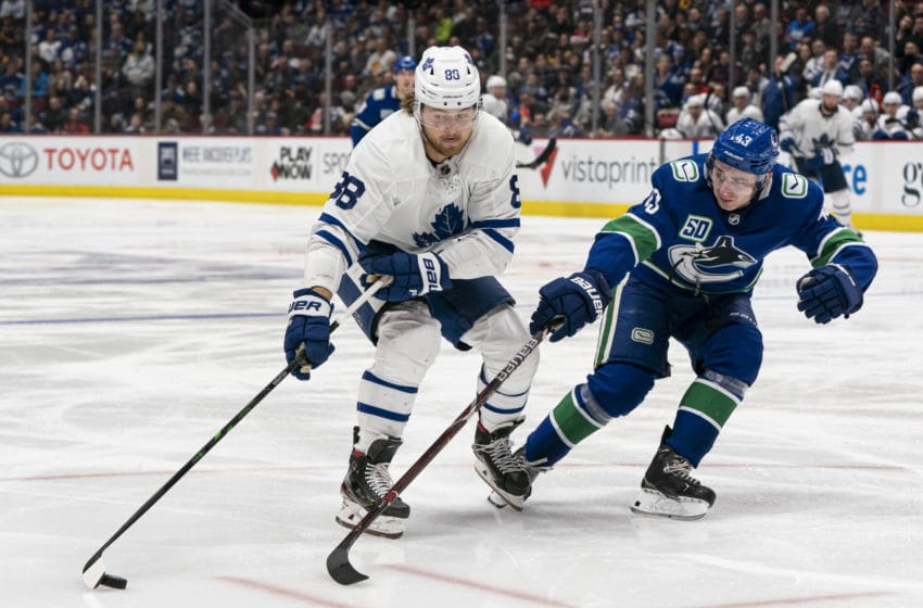 VANCOUVER, BC - DECEMBER 10: William Nylander #88 of the Toronto Maple Leafs tries to get around Quinn Hughes#43 of the Vancouver Canucks during NHL action at Rogers Arena on December 10, 2019 in Vancouver, Canada. (Photo by Rich Lam/Getty Images)