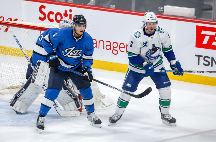 WINNIPEG, MB - JANUARY 14: Luca Sbisa #5 of the Winnipeg Jets and J.T. Miller #9 of the Vancouver Canucks keep an eye on the play during first period action at the Bell MTS Place on January 14, 2020 in Winnipeg, Manitoba, Canada. (Photo by Jonathan Kozub/NHLI via Getty Images)