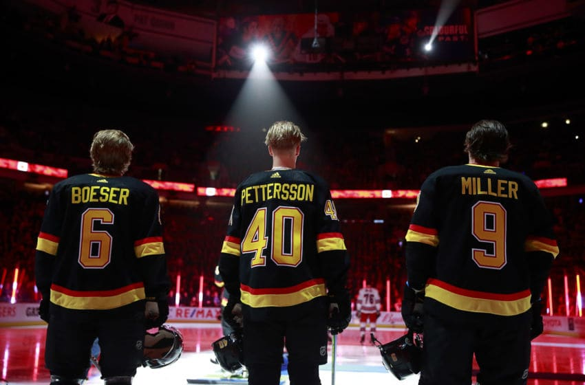VANCOUVER, BC - JANUARY 4: J.T. Miller #9, Elias Pettersson #40 and Brock Boeser #6 of the Vancouver Canucks listen to the national anthems during their NHL game against the New York Rangers at Rogers Arena January 4, 2020 in Vancouver, British Columbia, Canada. (Photo by Jeff Vinnick/NHLI via Getty Images)