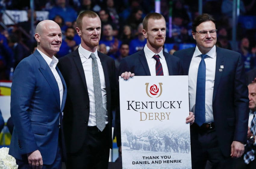 VANCOUVER, BC - FEBRUARY 12: Roberto and Paolo Aquilini present Henrik and Daniel Sedin with a gift during their jersey retirement ceremony before the NHL game between the Vancouver Canucks and the Chicago Blackhawks at Rogers Arena February 12, 2020 in Vancouver, British Columbia, Canada. (Photo by Jeff Vinnick/NHLI via Getty Images)