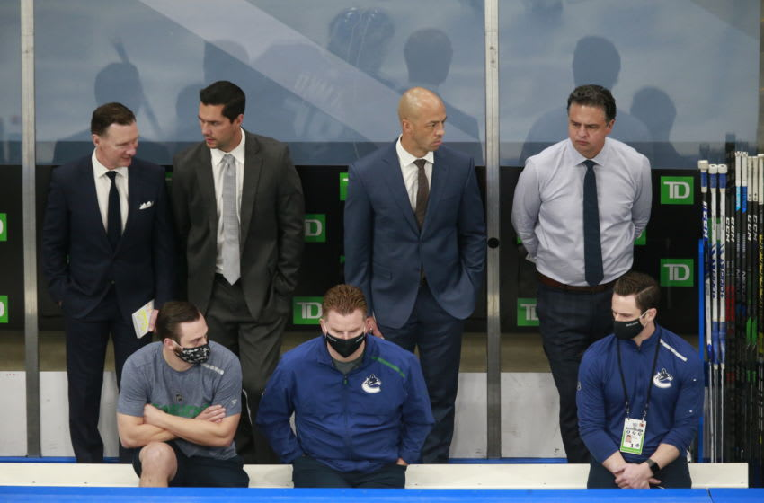 EDMONTON, ALBERTA - AUGUST 21: (L-R) Newell Brown, Nolan Baumgartner, Manny Malhotra and Travis Green of the Vancouver Canucks watch warm-ups prior to their game against the St. Louis Blues in Game Six of the Western Conference First Round during the 2020 NHL Stanley Cup Playoffs at Rogers Place on August 21, 2020 in Edmonton, Alberta. (Photo by Jeff Vinnick/Getty Images)
