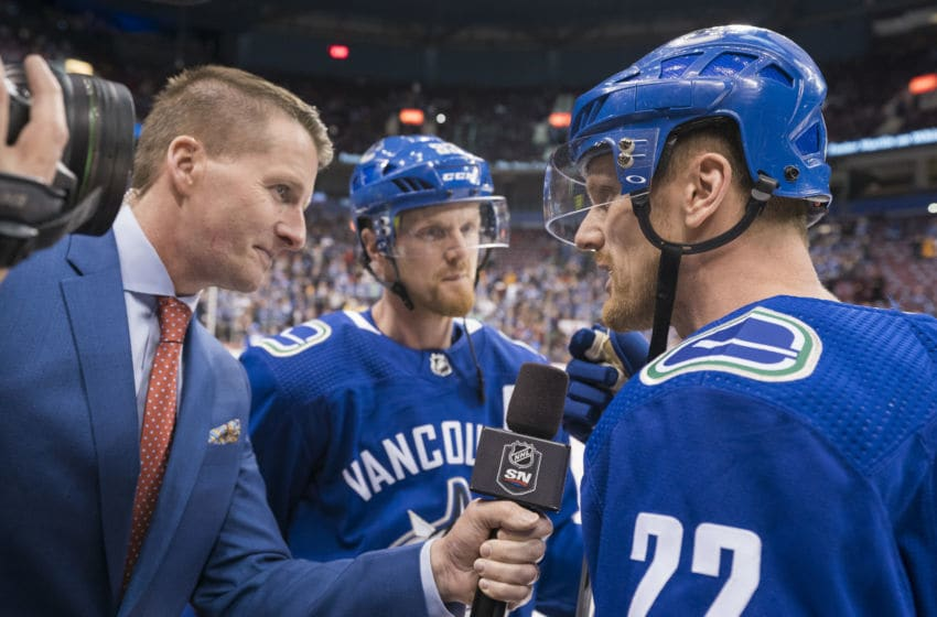 VANCOUVER, BC - OCTOBER 5: Daniel Sedin #22 and brother Henrik Sedin #33 of the Vancouver Canucks take to tv reporter Dan Murphy prior to their final home game against the Arizona Coyotes in NHL action on April, 5, 2018 at Rogers Arena in Vancouver, British Columbia, Canada. (Photo by Rich Lam/Getty Images)