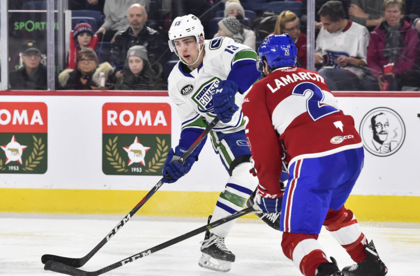 LAVAL, QC - MARCH 09: Kole Lind #13 of the Utica Comets looks to play the puck past Maxim Lamarche #2 of the Laval Rocket during the AHL game at Place Bell on March 9, 2019 in Laval, Quebec, Canada. The Laval Rocket defeated the The Utica Comets 5-3. (Photo by Minas Panagiotakis/Getty Images)