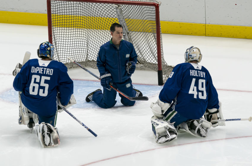 VANCOUVER, BC - JANUARY 4: Goalie coach Ian Clark of the Vancouver Canucks works with goalies Michael Dipietro #65 and Braden Holtby #49 on the first day of the Vancouver Canucks NHL Training Camp on January, 4, 2021 at Rogers Arena in Vancouver, British Columbia, Canada. (Photo by Rich Lam/Getty Images)
