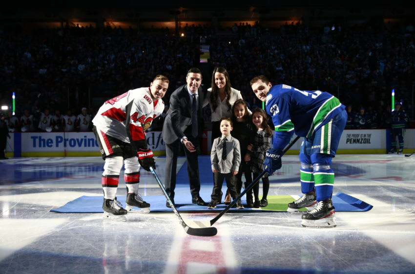 VANCOUVER, BC - DECEMBER 3: Alex Burrows and his family drop the puck in a ceremonial face-off between Bo Horvat #53 of the Vancouver Canucks and Jean-Gabriel Pageau #44 of the Ottawa Senators during their NHL game at Rogers Arena December 3, 2019 in Vancouver, British Columbia, Canada. (Photo by Jeff Vinnick/NHLI via Getty Images)