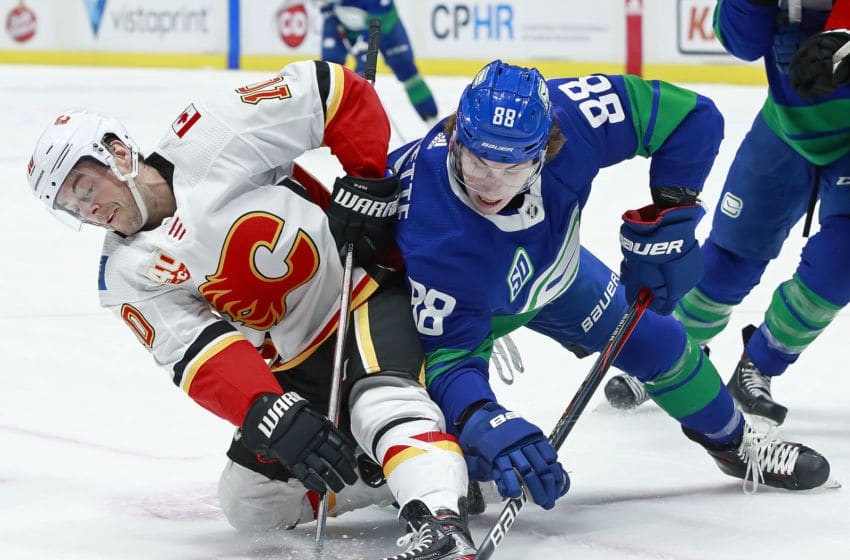 VANCOUVER, BC - FEBRUARY 8: Adam Gaudette #88 of the Vancouver Canucks checks Derek Ryan #10 of the Calgary Flames during their NHL game at Rogers Arena February 8, 2020 in Vancouver, British Columbia, Canada. (Photo by Jeff Vinnick/NHLI via Getty Images)