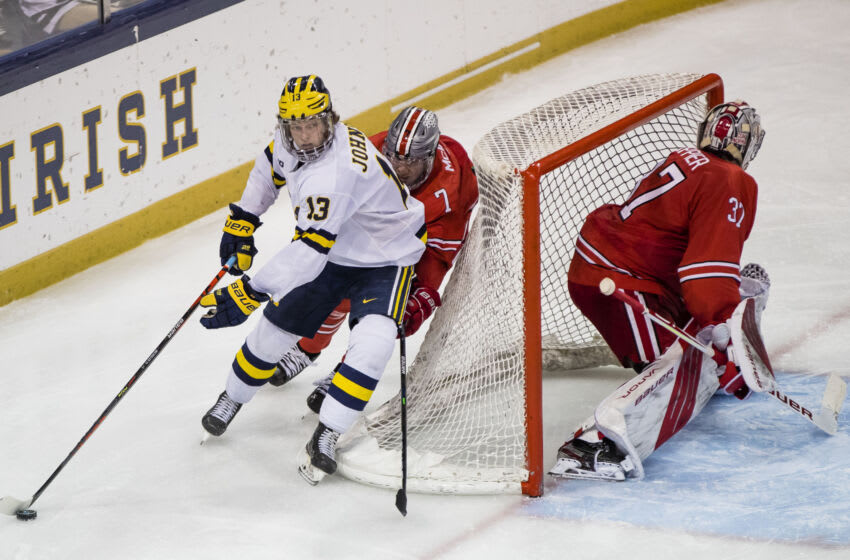 Mar 14, 2021; South Bend, IN, USA; Michigan's Kent Johnson (13) wraps around the net as Ohio State's Evan McIntyre (7) chases him during the Michigan vs. Ohio State Big Ten Hockey Tournament game Sunday, March 14, 2021 at the Compton Family Ice Arena in South Bend. Mandatory Credit: Michael Caterina-USA TODAY Sports