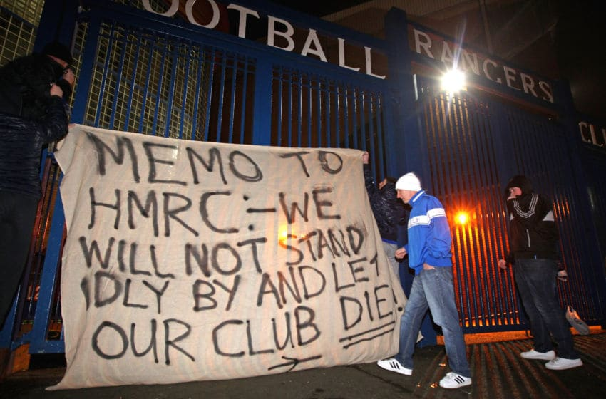GLASGOW, SCOTLAND - FEBRUARY 14: Fans raise a banner on the gates of Ibrox Stadium on February 14, 2012 in Glasgow, Scotland. HM Revenue and Customs lodged a petition at the Court of Session to put Glasgow Rangers Football Club into administration. This counteracts moves by owner Craig Whyte, who yesterday gave notice of the clubs intent to go into administration. HMRC is in dispute with the Scottish Premier League Champions over a £49million pound tax bill. (Photo by Jeff J Mitchell/Getty Images)