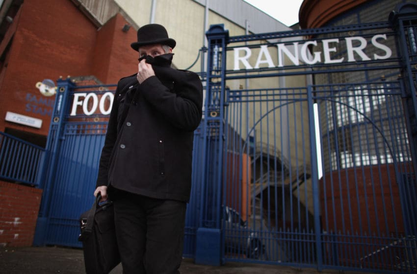 GLASGOW, SCOTLAND - FEBRUARY 17: A man dressed in a bowler hat carrying a briefcase walks past the Ibrox Stadium gates on February 17, 2012 in Glasgow, Scotland. Rangers face Kilmarnock on Saturday following a week where the club went officially into administration, incurring a 10 point penalty from the Scottish Premier League. (Photo by Jeff J Mitchell/Getty Images)
