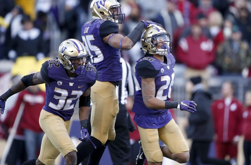 Nov 27, 2015; Seattle, WA, USA; Washington Huskies defensive back Sidney Jones (26) gets a pat on the helmet from defensive back Brian Clay (35) after Jones returned an interception 69-yards for a touchdown against the Washington State Cougars during the third quarter at Husky Stadium. At left is Washington Huskies defensive back Budda Baker (32). Washington beat Washington State 45-10. Mandatory Credit: Jennifer Buchanan-USA TODAY Sports
