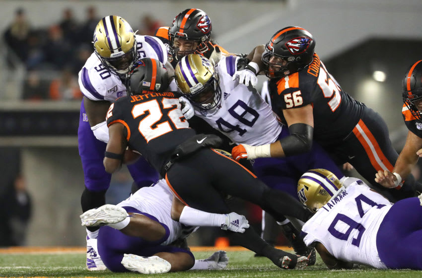 CORVALLIS, OREGON - NOVEMBER 08: Jermar Jefferson #22 of the Oregon State Beavers is tackled by the Washington Huskies in the fourth quarter during their game at Reser Stadium on November 08, 2019 in Corvallis, Oregon. (Photo by Abbie Parr/Getty Images)