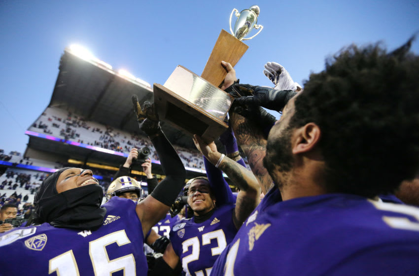 SEATTLE, WASHINGTON - NOVEMBER 29: The Washington Huskies celebrate with the Apple Cup trophy after defeating the Washington State Cougars 31-13 during their game at Husky Stadium on November 29, 2019 in Seattle, Washington. (Photo by Abbie Parr/Getty Images)