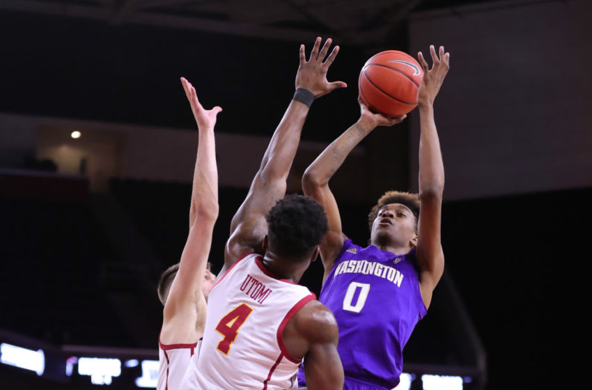 LOS ANGELES, CALIFORNIA - FEBRUARY 13: Jaden McDaniels #0 of the Washington Huskies handles the ball against Nick Rakocevic #31 and Daniel Utomi #4 of the USC Trojans during a college basketball game at Galen Center on February 13, 2020 in Los Angeles, California. (Photo by Leon Bennett/Getty Images)