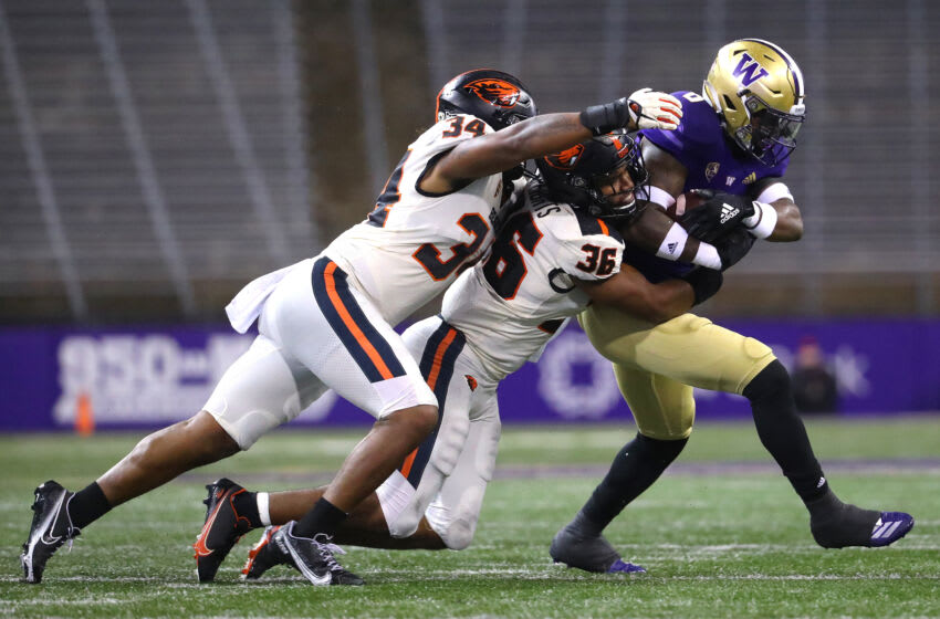 SEATTLE, WASHINGTON - NOVEMBER 14: Richard Newton #6 of the Washington Huskies is tackled by Avery Roberts #34 and Omar Speights #36 of the Oregon State Beavers in the first half at Husky Stadium on November 14, 2020 in Seattle, Washington. (Photo by Abbie Parr/Getty Images)